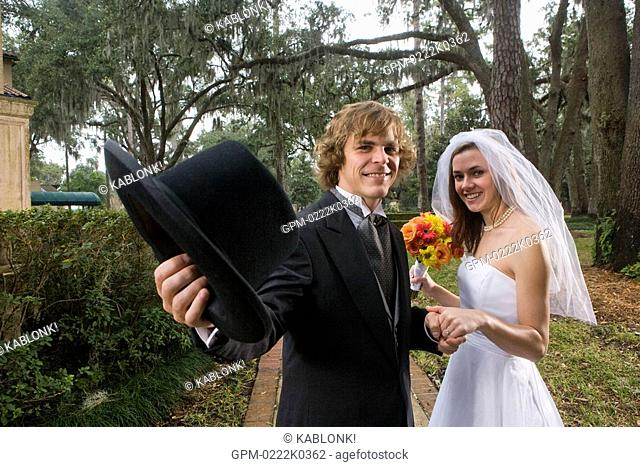 Portrait of happy bride and groom standing outside on wedding day