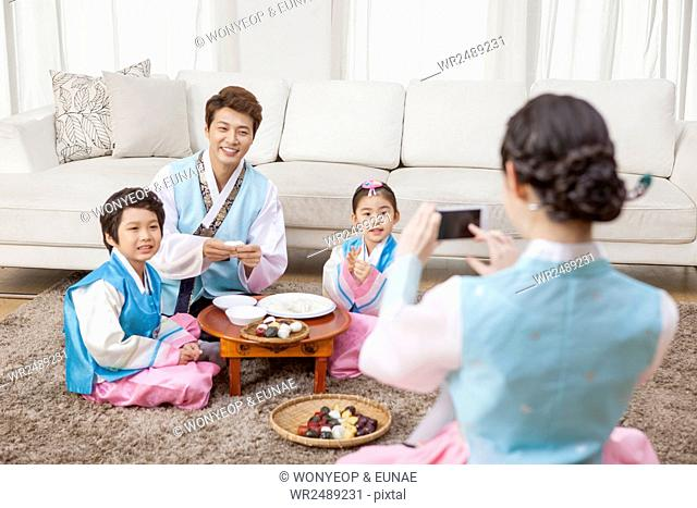 Korean mother taking picture of her family in traditional Korean clothes