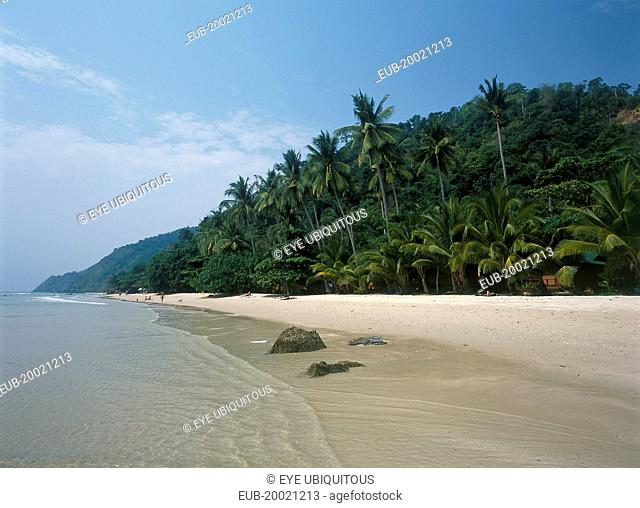 White Sand Beach, Haad Sai Khao. View along sandy shore with lush green trees growing inland
