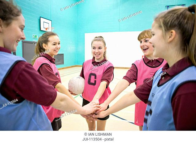 Smiling high school students touching hands in huddle before netball game