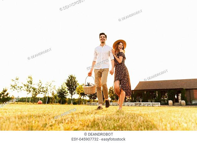 Happy young couple with basket of drinks and food going to have picnic outdoors
