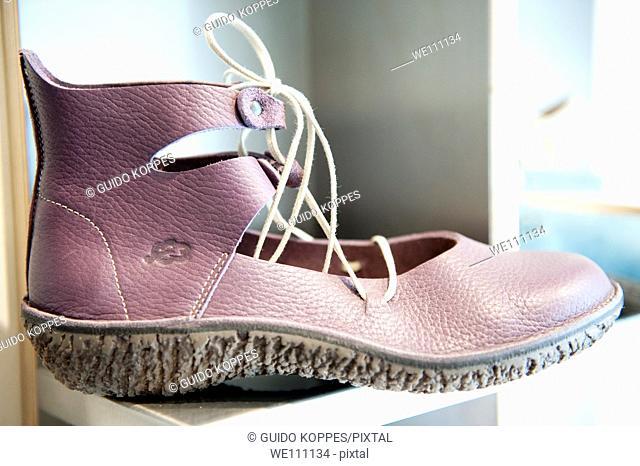 A woman's shoe on a shelf in the Tilburg based fair trade shoe shop: 'Pijnenburg Shoes'