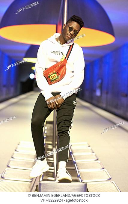 young fashionable man standing indoors in underground, in Munich, Germany