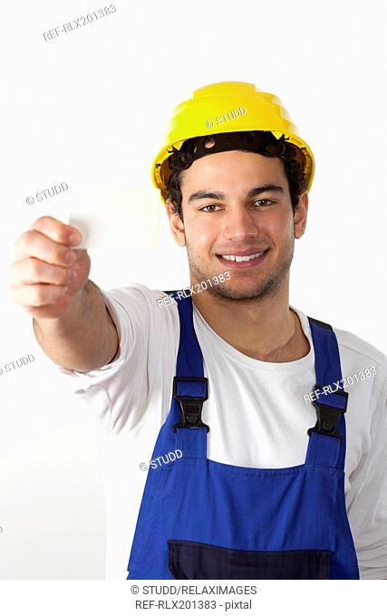 Young construction worker holding card business