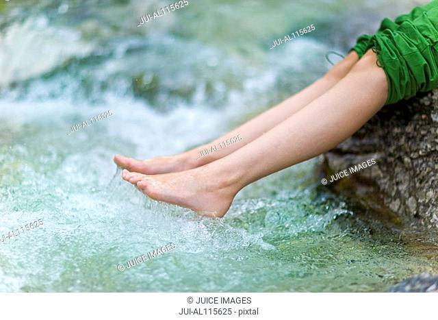 Teenage girl sitting on rock with feet in water