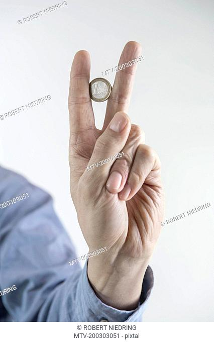 Businessman holding one euro coin between two fingers, Bavaria, Germany