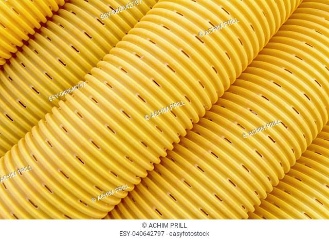 full frame detail of a yellow drainage pipe