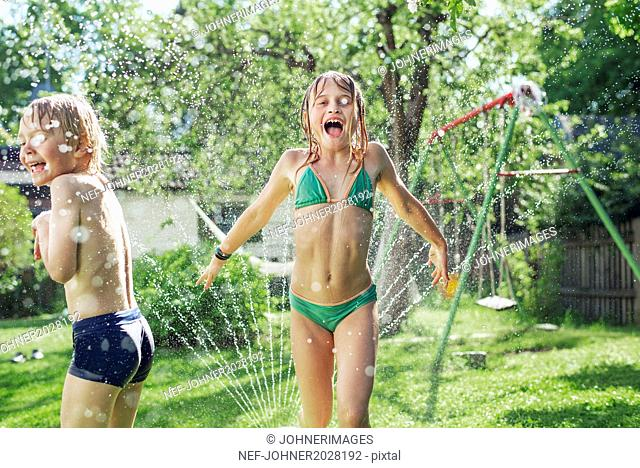 Girl and boy playing with water in garden