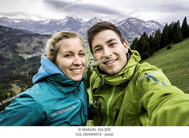 Young hiking couple taking self portrait, on the way down Zinken mountain, Oberjoch, Bavaria, Germany