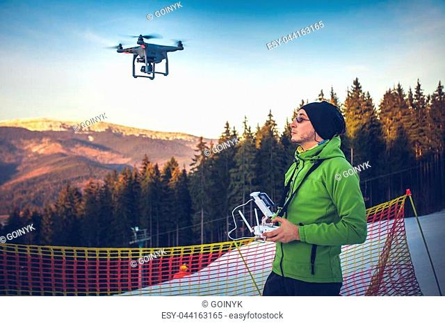 Young man in green jacket operating a drone using a remote controller. Ski resort in the background, winter landscape with pine tree forest and mountains