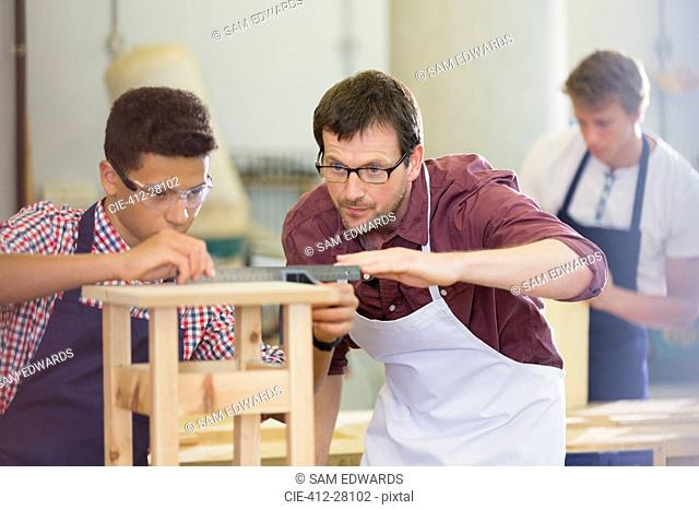 Focused carpenters measuring wood in workshop