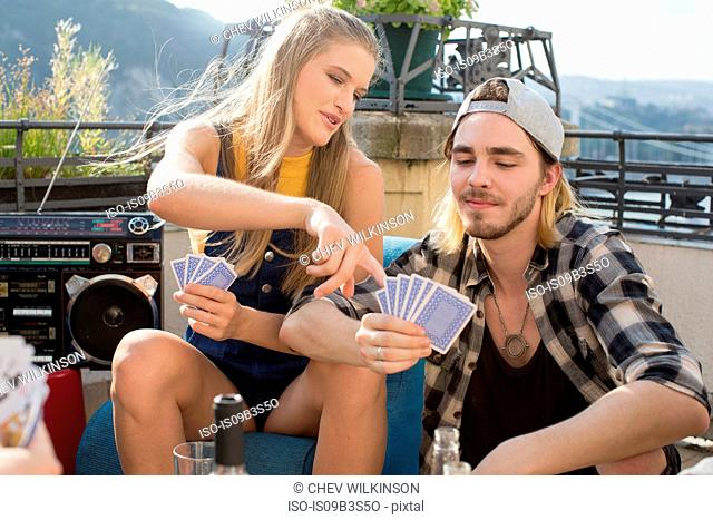 Young couple playing card game at roof terrace party, Budapest, Hungary