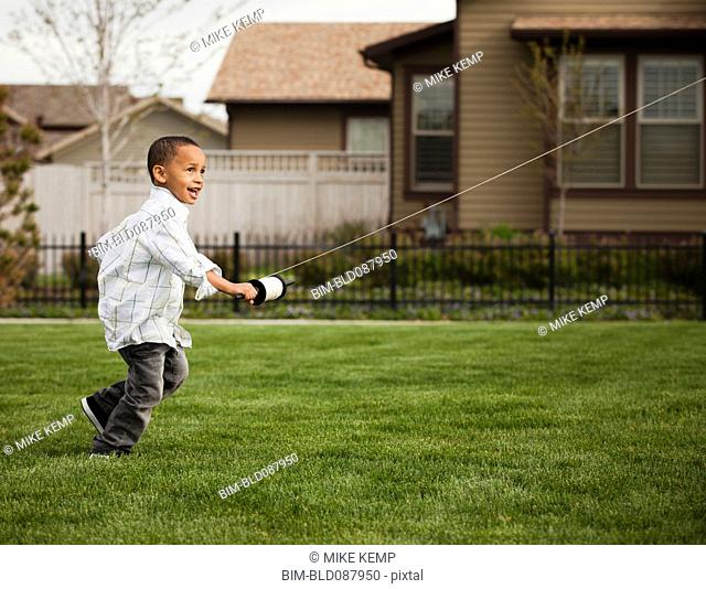 Mixed race boy flying kite