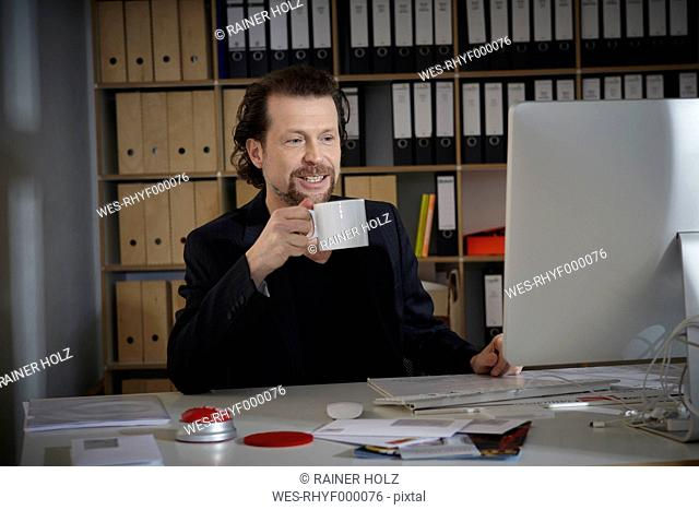 Germany, Cologne, Mature man with coffee cup in office, smiling