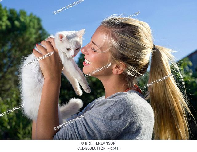 Young woman smiles holding kitten