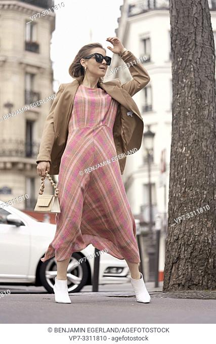 fashionable blogger woman at street during fashion week, in city Paris, France