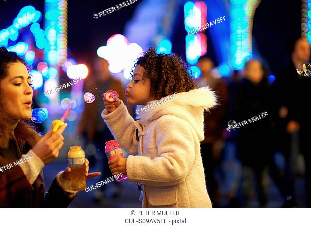 Mother and daughter blowing bubbles, at funfair