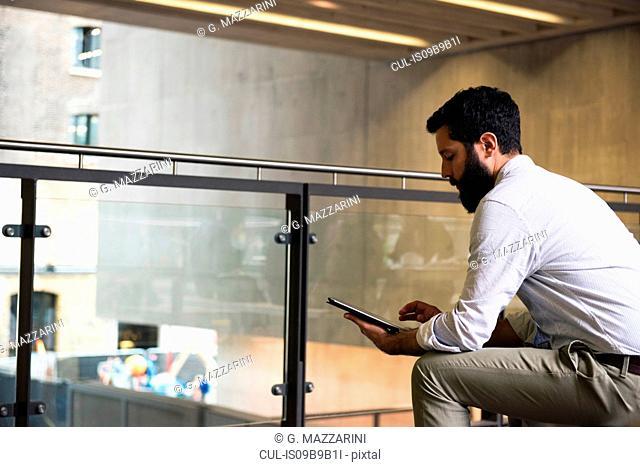 Man on mezzanine in office building using digital tablet