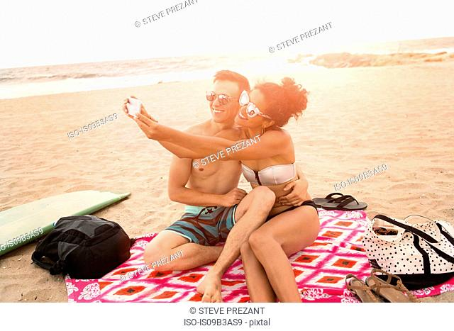 Young couple taking smartphone selfie on Rockaway Beach, New York State, USA