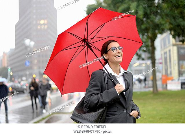 Germany, Berlin, happy businesswoman with red umbrella at Potsdamer Platz
