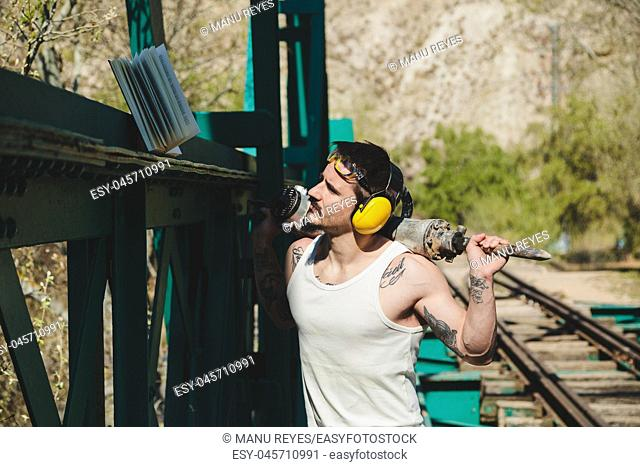 Young construction worker man reading a book on an old steel railway bridge with a hydraulic hammer in his shoulders