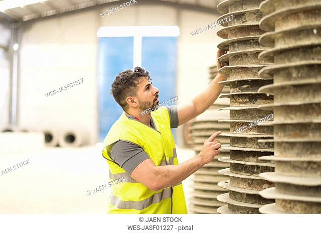 Worker in a factory looking at material