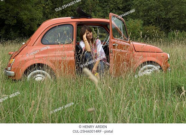 Relaxed female sitting in car in field