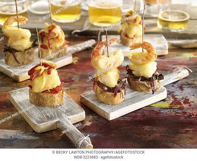 tapas de bacalao con pimientos y gambas con vasos de cerveza / Cod with peppers and prawns with beer glasses