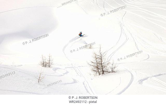 Man snowboarding downhill in powder snow