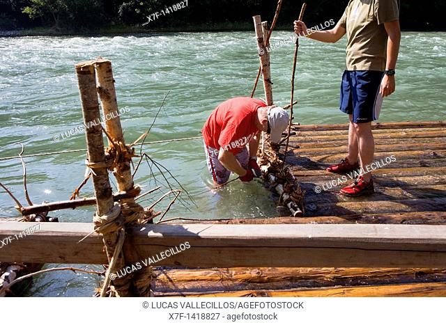 ferrymen almadieros or raiers making a raft rai or almadia  La Pobla de Segur  Diada dels Raiers ferrymen feast day  Noguera Pallaresa river  Pyrénées  Lleida...