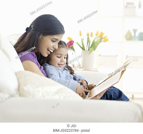 Hispanic mother reading to daughter