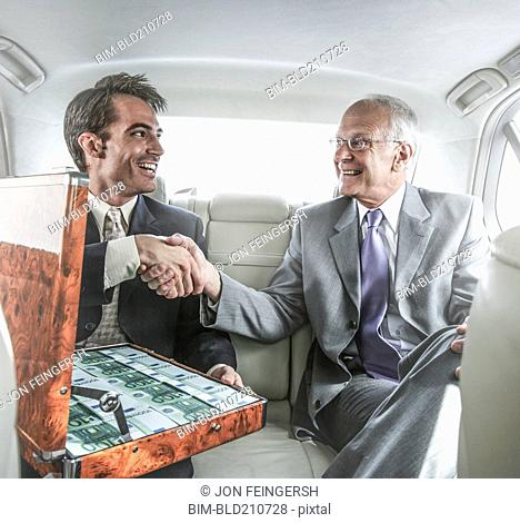 Businessmen shaking hands in backseat of car