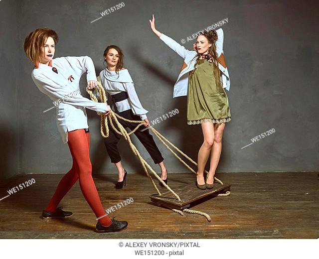 Young girls having fun in the Studio. They are trendy long shirts and coats. The collection of clothes is provided by a known fashion designer from Belarus
