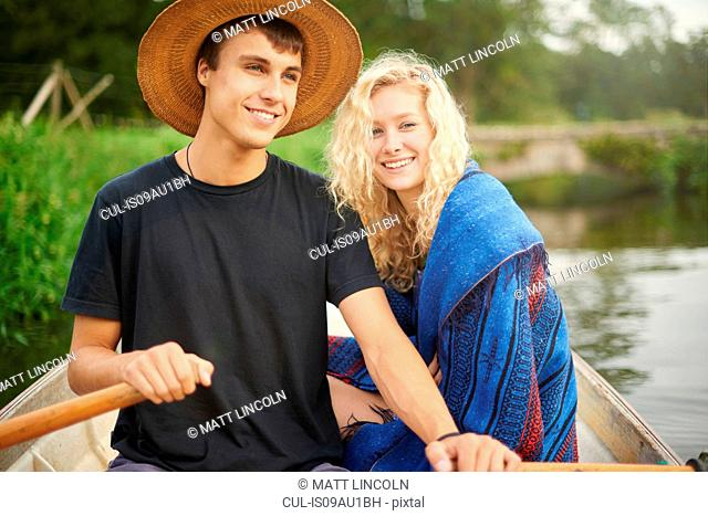 Portrait of young couple in river rowing boat