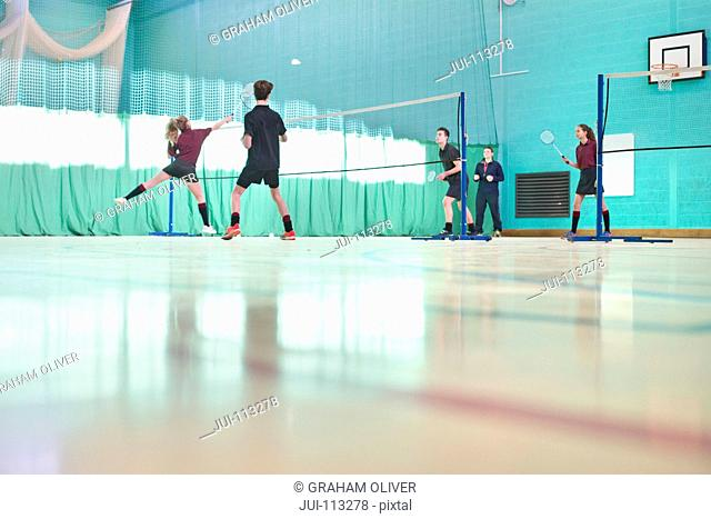 High school students playing badminton in gym class