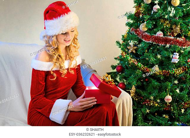 Young woman opening christmas present