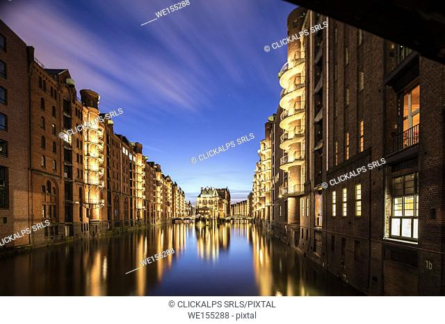 Blue dusk and lights are reflected in Poggenmühlenbrücke with water castle between bridges Altstadt Hamburg Germany Europe