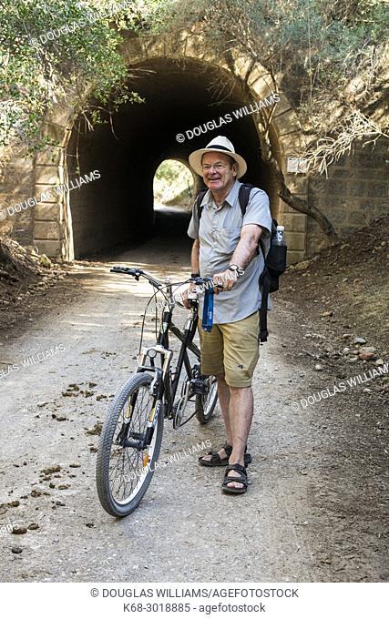 A male cyclist, 65, near a tunnel on the Via Verde de la Sierra, Cadiz, Spain, bicycling route