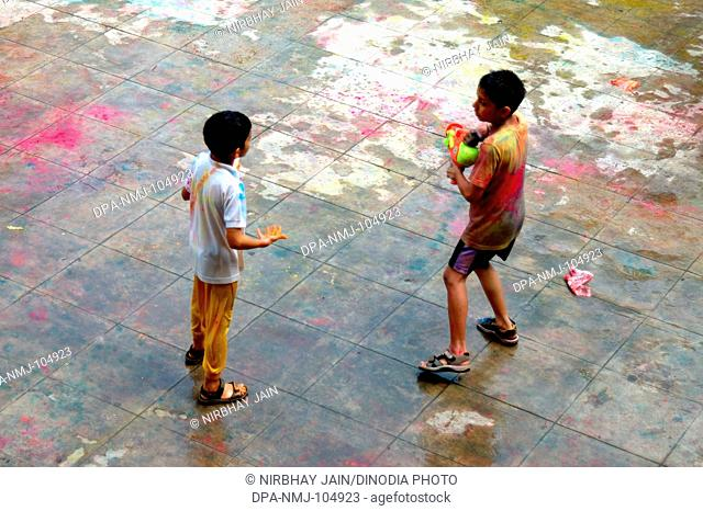 Two children playing Holi festival of color at Ananta apartments at Breach Candy  ; Bombay Mumbai  ; Maharashtra  ; India