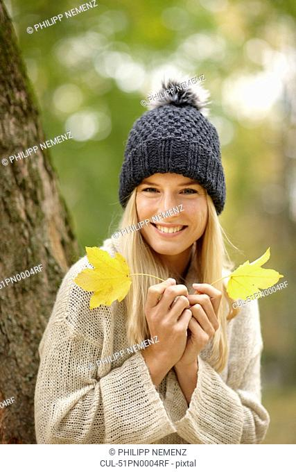 Woman holding autumn leaves outdoors