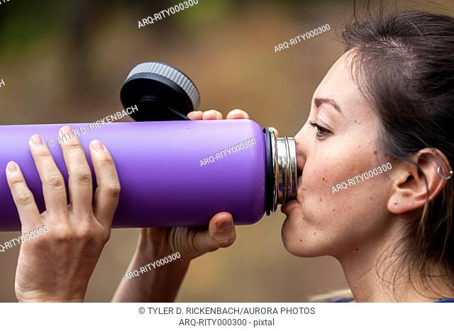 Profile headshot of woman with black hair drinking water from bottle after trail running