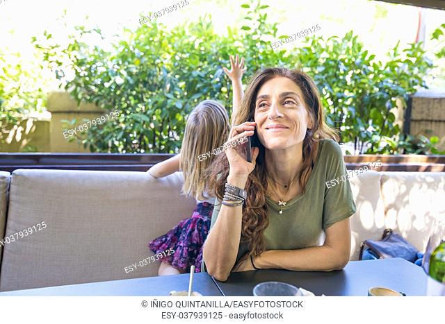 happy woman with green shirt and next to little girl, talking on mobile phone sitting in terrace of restaurant or cafe