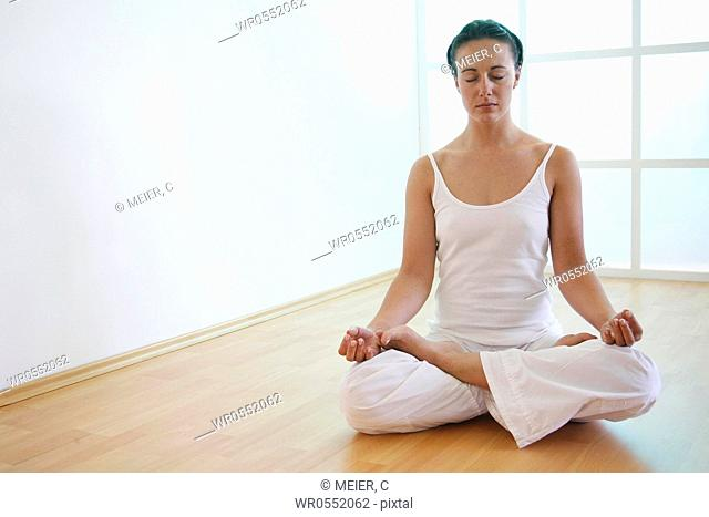Young woman meditates in lotus position on the floor