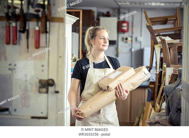 A young woman in a workshop, holding two packages wrapped in brown packaging paper, ready for despatch