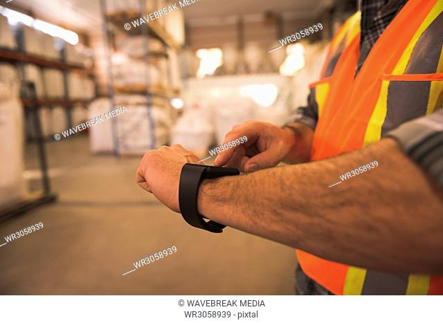 Man in protective workwear using smartwatch