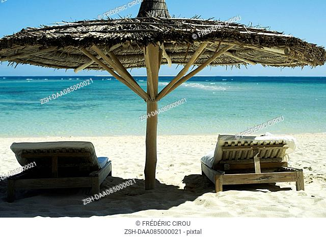 Beach chairs shaded by thatched umbrella