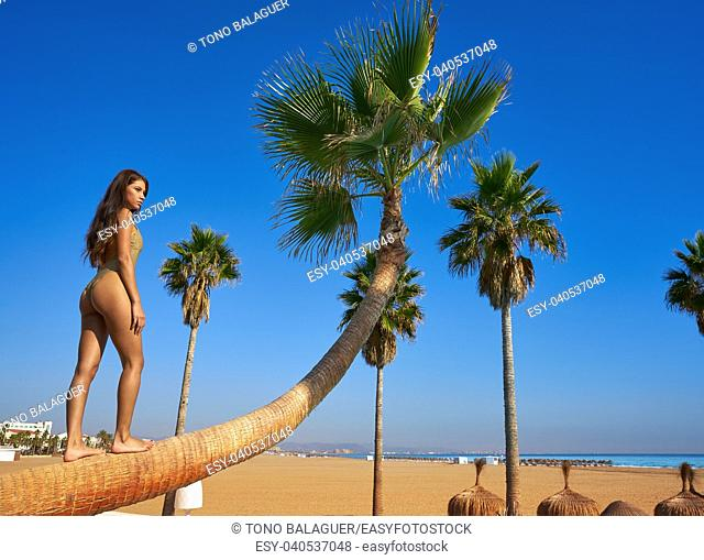 Beautiful woman standing on bent palm tree trunk at the beach