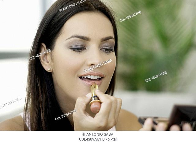 Close up of young woman applying lipstick