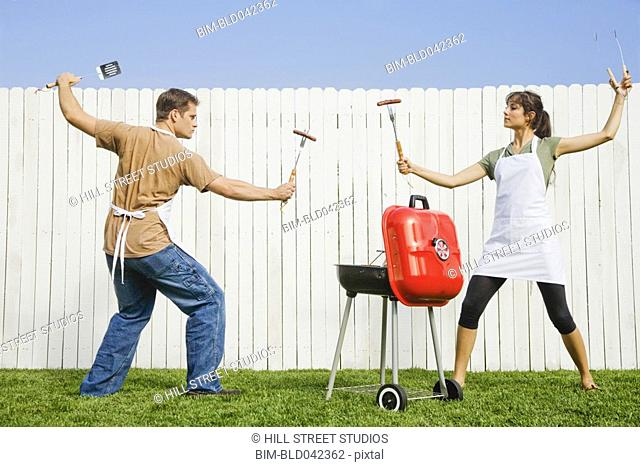 Multi-ethnic couple in fighting stance with barbeque utensils