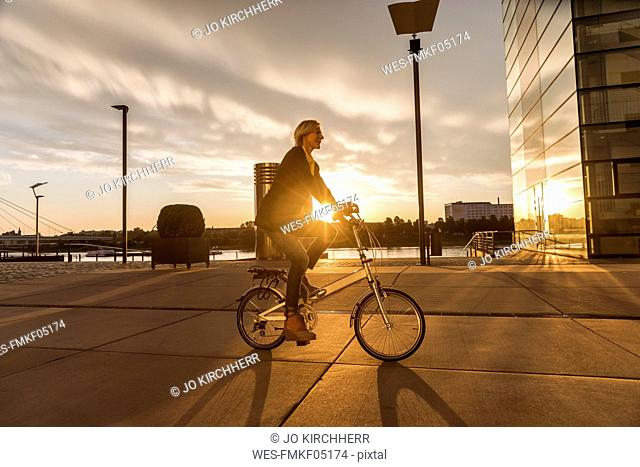 Senior woman riding city bike at the riverside at sunset